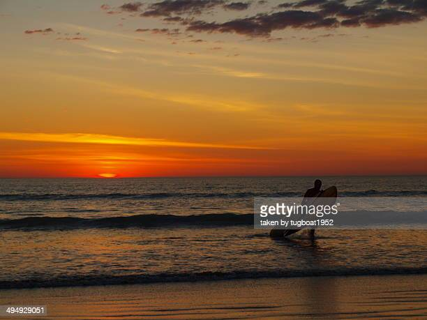 Board rider coming out of water at sunset