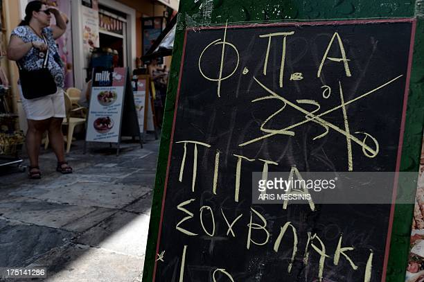 A board with a handwrite announcement of the reduction of the VAT has been placed at a restaurant of Athens on August 1 2013 Hoping to boost...
