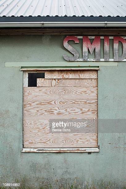 A boarded up window of a run down building