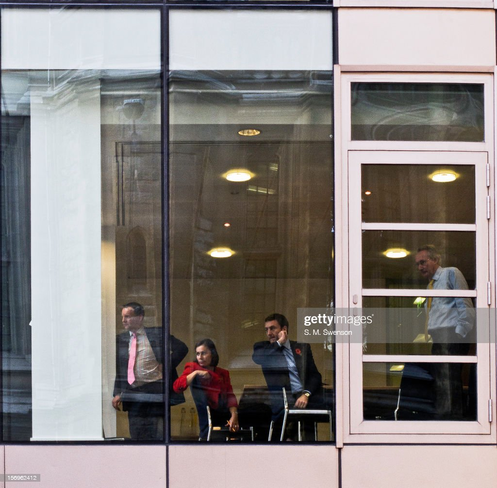 Boardroom executives overlooking students protesting against the trebling of tuition fees, cutbacks to education and overall austerity. Located in the City of London (financial district). Fetter Lane, London, England, November 2011