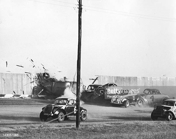 Boards fly through the air as a car crashes into the wooden fence surrounding Strawberry Hill Speedway during a wild Modified stock car race crash