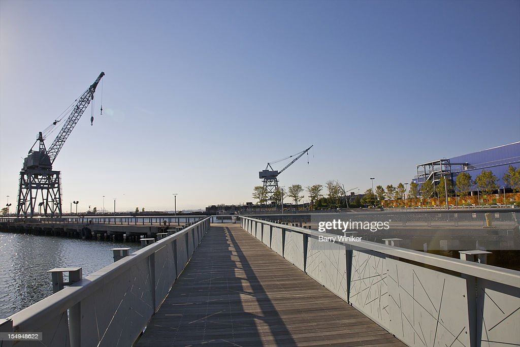 Boardwalk atop water near maritime structures. : Stock Photo