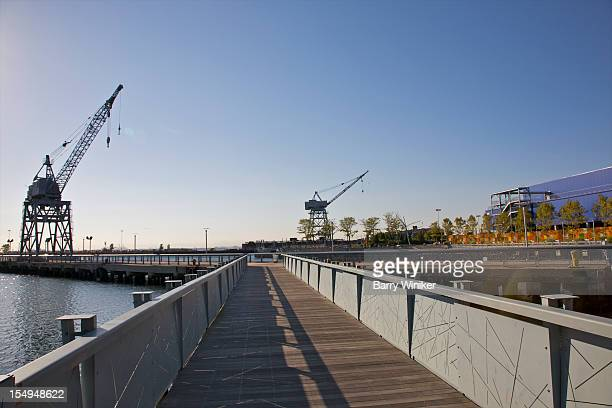 Boardwalk atop water near maritime structures.