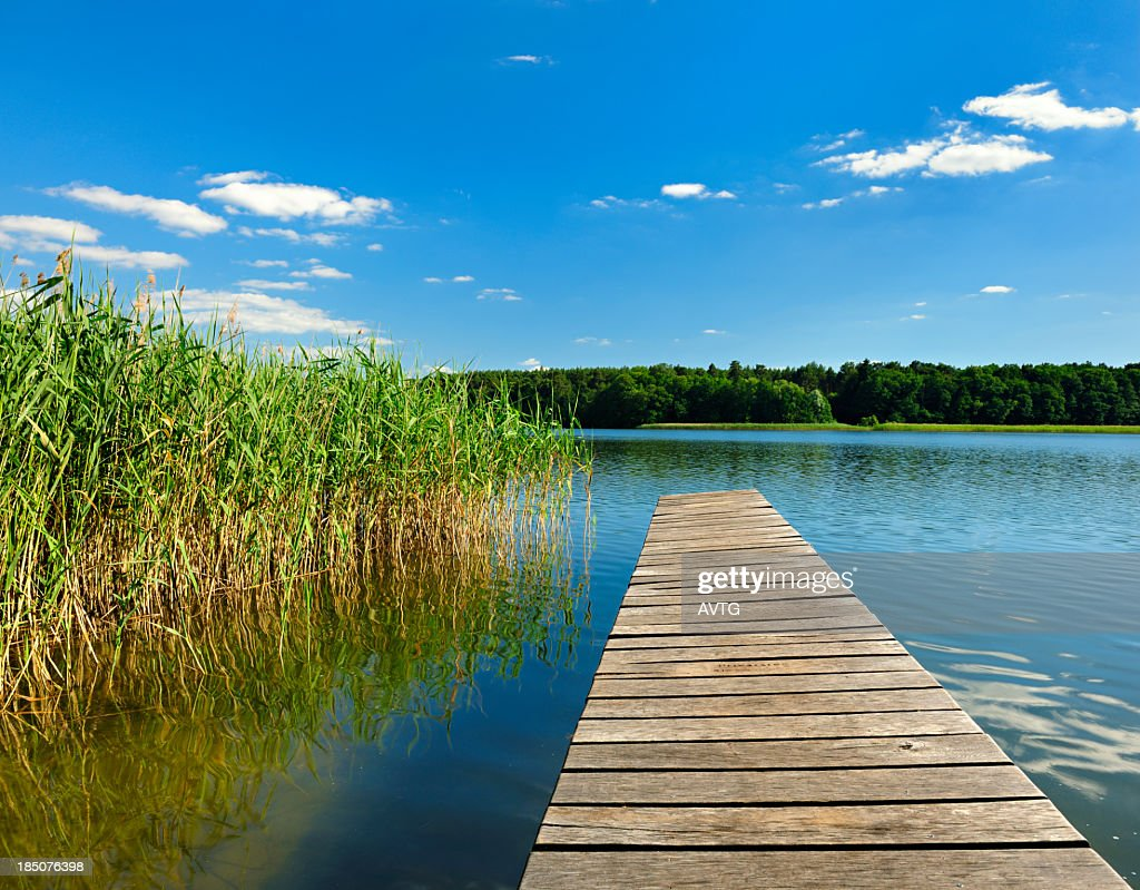 Boardwalk Dock on Lake under Cloudy Summer Sky