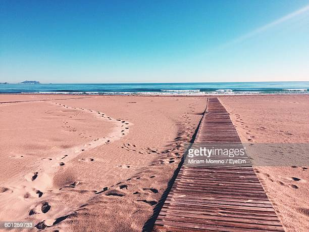 Boardwalk On Beach Against Blue Sky