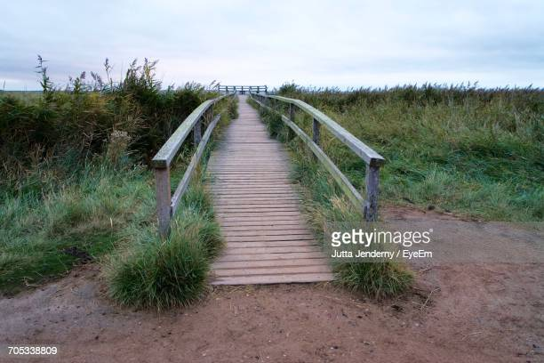 Boardwalk On Grassy Field Against Sky