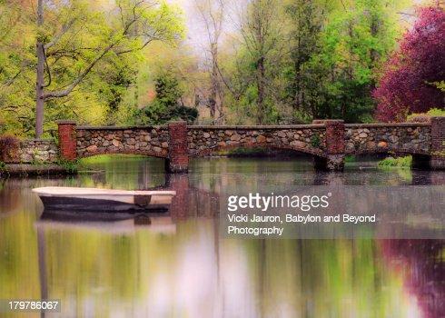 Boat Adrift in Front of Bridge on Calm Water