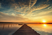 Boat and wooden jetty on lake with a reflection in the water at sunset