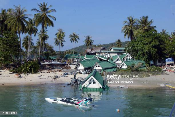 A boat and one of the gift shops building submerge on the beach of Phi Phi island in southern Thailand's holiday resort which was destroyed by a...