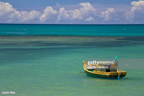Boat at the green sea of Espelho Beach
