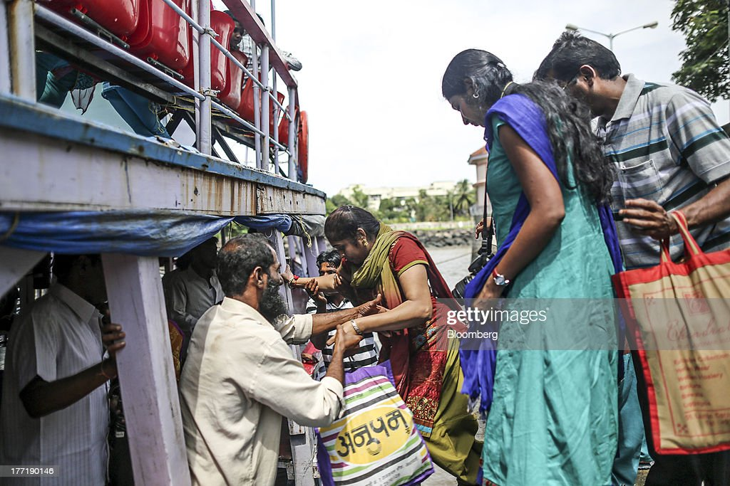 A boat attendant helps people board a ferry near the Gateway of India memorial building in Mumbai, India, on Wednesday, Aug. 21, 2013. The prospect of an indecisive 2014 election in India is eroding confidence among global investors that the government can stop the rupees worst drop in more than two decades. Photographer: Dhiraj Singh/Bloomberg via Getty Images