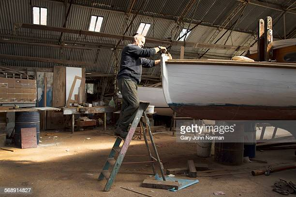 Boat builder working on a boat.