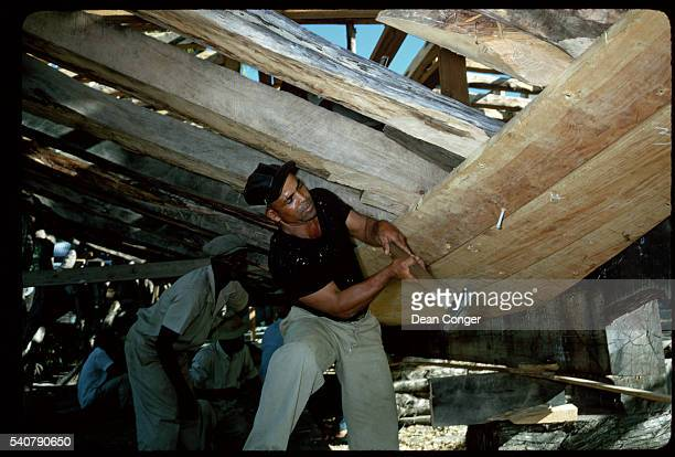 Boat builders use sledgehammers to pound spikes to hold planking onto ribs of a new wooden boat Grenada | Location Grenada