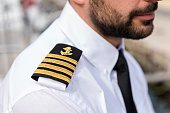 Horizontal color image of young boat captain, close-up of shoulder epaulette.
