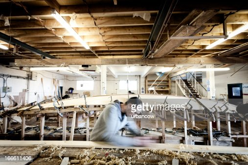 Boat carpenter, using a wood plane : Stock Photo