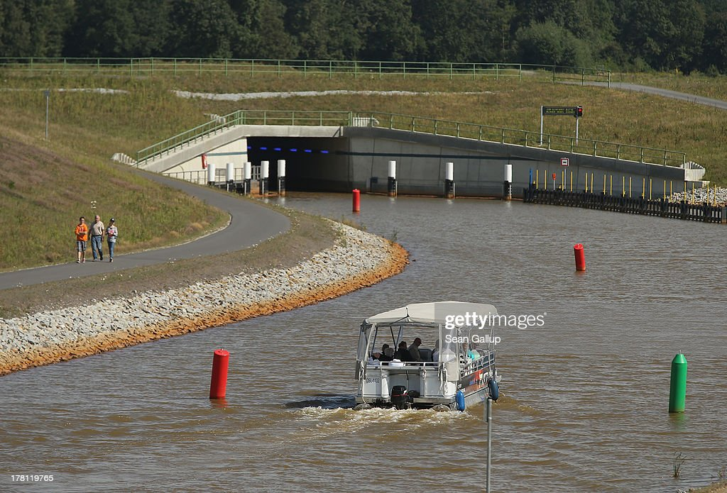 A boat carries tourists on a canal linking artificial Senftenberger See and Geierswalder See lakes on August 26, 2013 near Grosskoschen, Germany. Senftenberger See was once an open-pit lignite coal mine flooded after it shuttered in the late 1960s, and today it is popular among tourists, wind surfers and fishermen. In a development project initiated by state government, other nearby former open-pit mines that once evoked a lunar landscape are being turned into lakes in a long-term rejuvenation effort that is also intended to make the area a viable tourist destination. Mineral residue in the mines, however, is proving a difficult stumbling block that is making many of the new lakes too acidic to sustain marine life in the short term.