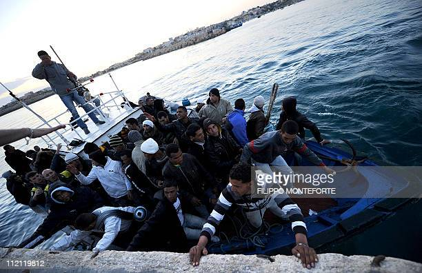 A boat carring Tunisian migrants enters the port of Lampedusa on April 12 2011 Around 26000 undocumented migrants have arrived in Italy so far this...