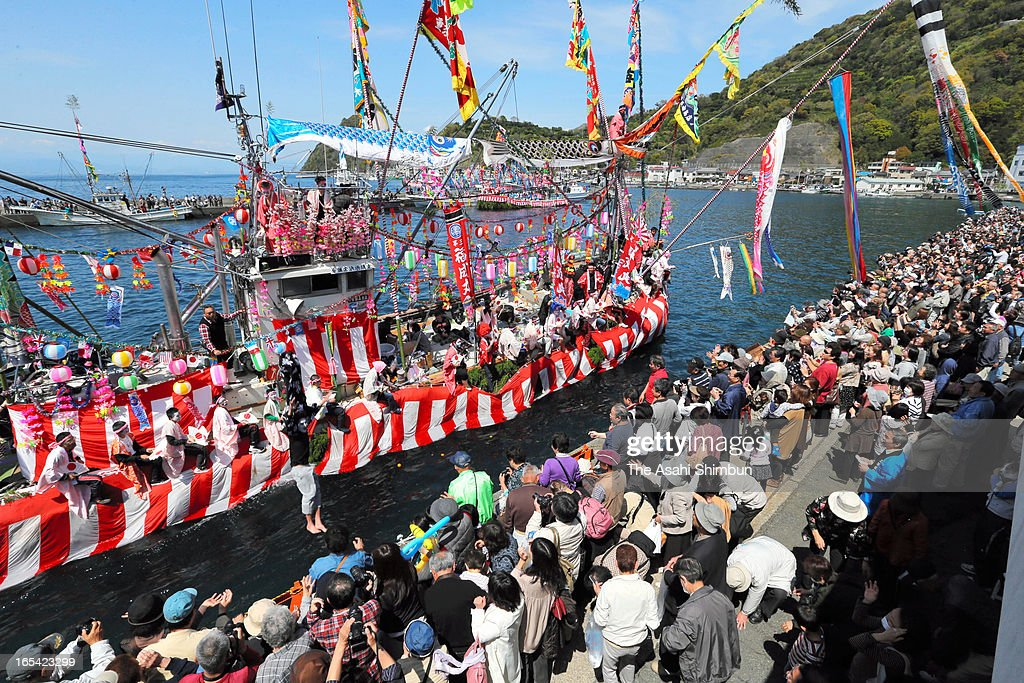 A boat carrying fishermen and boys dressed and make-up as women dance arrives at a shore during annual Ose Festival at Suruga Bay on April 4, 2013 in Numazu, Shizuoka, Japan. The festival, to pray for the safety at sea and good harvest, is held April 4 every year.