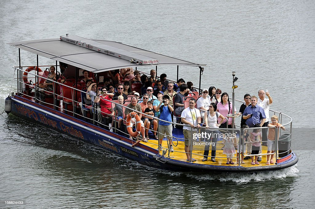 A boat carrying tourists sails in the Singapore River in Singapore, on Saturday, Dec. 29, 2012. Singapore may grapple with elevated inflationary pressures for a third year in 2013, reducing scope for the central bank to provide stimulus to an economy that probably entered a technical recession this quarter. Photographer: Munshi Ahmed/Bloomberg via Getty Images