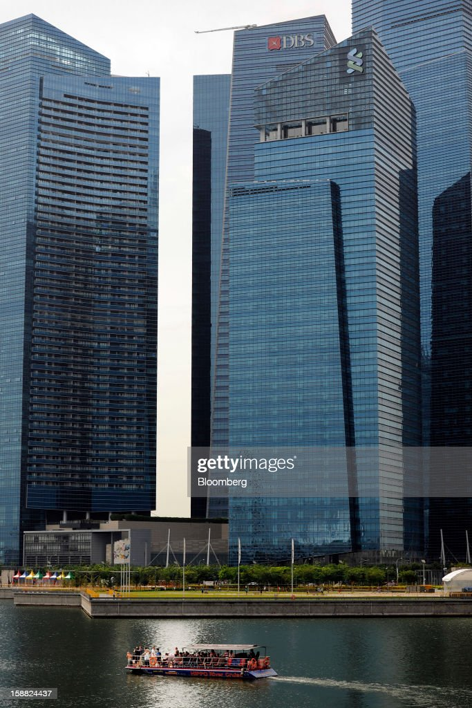 A boat carrying tourists sails past the Marina Bay Financial Centre in the central business district in Singapore, on Saturday, Dec. 29, 2012. Singapore may grapple with elevated inflationary pressures for a third year in 2013, reducing scope for the central bank to provide stimulus to an economy that probably entered a technical recession this quarter. Photographer: Munshi Ahmed/Bloomberg via Getty Images