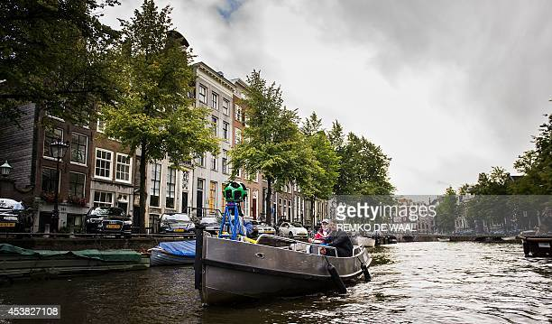 A boat containing a 360degree Google camera navigates through the canals of Amsterdam on August 19 2014 The camera mounted on a vessel takes photos...