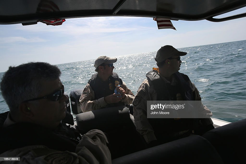 A boat crew from the U.S. Office of Air and Marine (OAM) looks towards a suspicious boat just across the Mexican border in the Gulf of Mexico on April 12, 2013 near Port Isabel, Texas. The crew patrols coastline waters near the U.S.-Mexico border searching for drug smugglers as well as illegal immigrants, which come across from Mexico near the mouth of the Rio Grande River. The Midnight Express interceptor is a 39 foot 900 horsepower craft capable of chasing smugglers down at 55 knots (63 mph). OAM units also push back illegal fishing boats out of U.S. waters.
