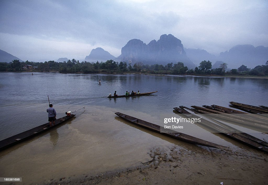 A boat crosses the river at Vang Vieng in Vientiane Province a two and a half hour drive from the capital of Laos Known as the 'small Lao Guilin'...