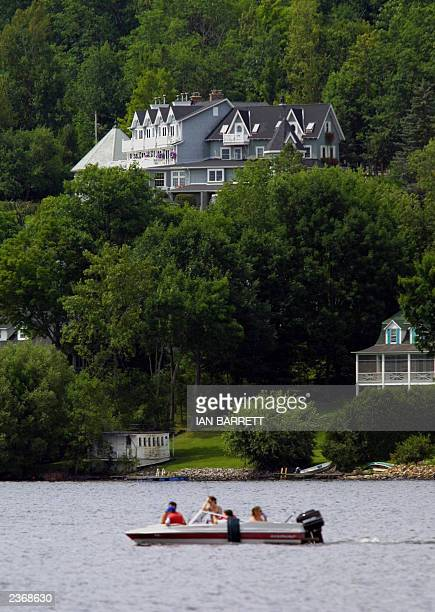 A boat cruises on Lake Massawippi 04 August under the shadow of L'Auberge Hatley the exclusive hotel where French President Jacques Chirac has been...