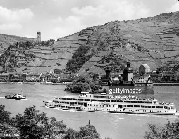 Boat floating by Pfalzgrafenstein Castle on the Rhine river near Kaub Germany 1955