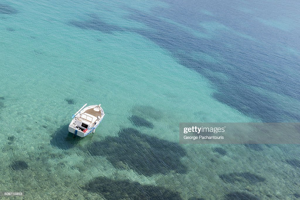 Boat floating on green waters