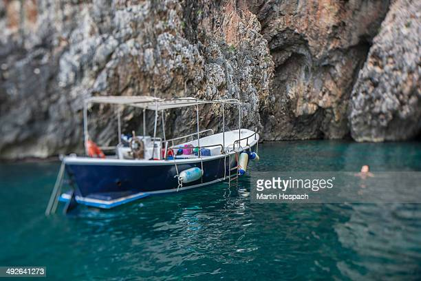 Boat floating on water by rock formation