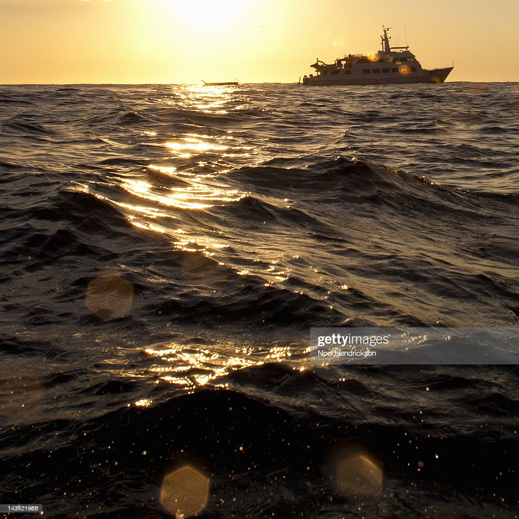 A boat floats in the middle of the ocean : Stock Photo