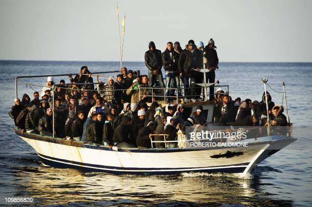 A boat full of would be immigrants is seen near the Italian island of Lampedusa on March 7 2011 A total of 155 immigrants landed on the Italian...