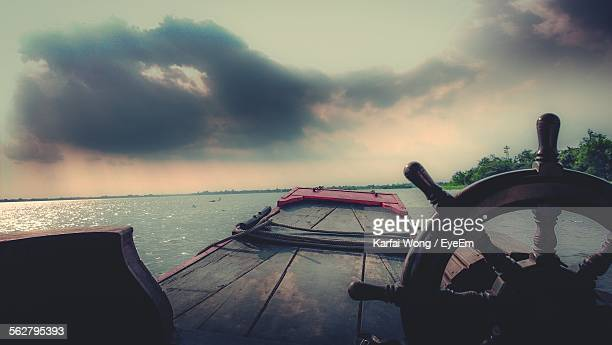 Boat In Mekong River Against Cloudy Sky