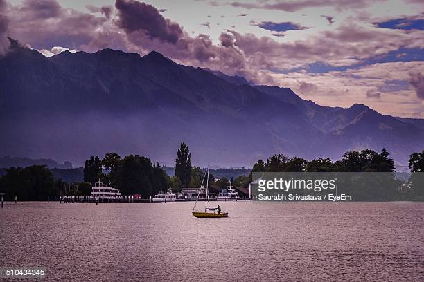 Boat in river against trees and mountain range