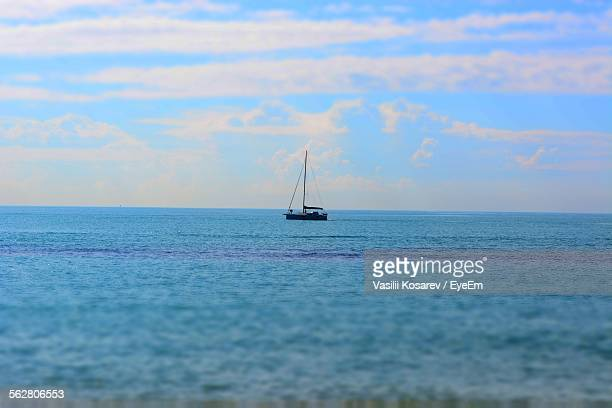 Boat In Sea Against Cloudy Sky