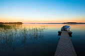 Colourful sunset on calm lake with boat in foreground (Kerimäki, Finland)