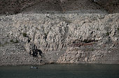 A boat is dwarfed by the tall bleached 'bathtub ring' on the rocky banks of Lake Mead on May 12 2015 in Lake Mead National Recreation Area Nevada As...