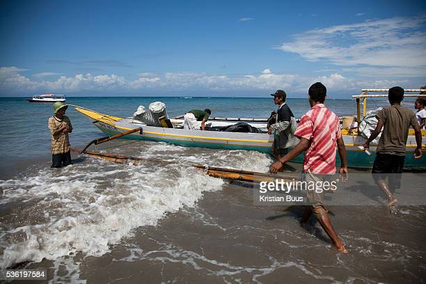 A boat is picking up goods and school children to ferry them from school and to their home further up the coast on the island Atauro Atauro is an...
