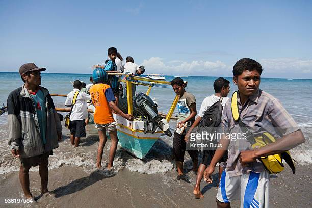 A boat is picking up goods and school children to ferry them from school and home further up the coast on the island Atauro Atauro is an island with...