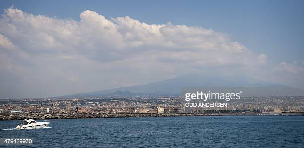 A boat is seen approaching the harbour in Catania with Mount Etna rising into the cloud behind on July 4 2015 AFP PHOTO / ODD ANDERSEN