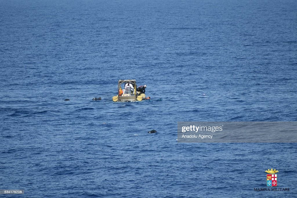 A boat is seen as Bettica and Bergamini ships of Italian Navy rescue migrants from an overcrowded boat which was about to capsize at Sicilian Strait, between Libya and Italy, in Mediterranean sea on May 25, 2016. The Italian Navy saved around 500 migrants as they found dead bodies of seven migrants in the sea during the operations.