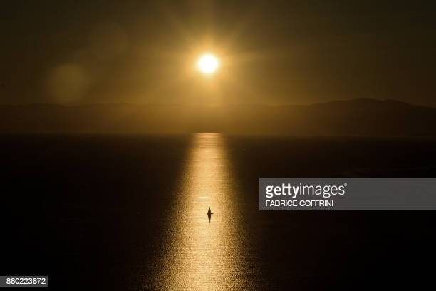 A boat is seen at sunset on Lake Geneva from Chexbres western Switzerland on October 11 2017 / AFP PHOTO / Fabrice COFFRINI