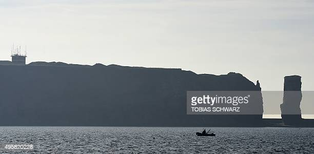 A boat is seen off the shore of the German North Sea island of Helgoland and its 'Lange Anna' stack on November 4 2015 AFP PHOTO / TOBIAS SCHWARZ