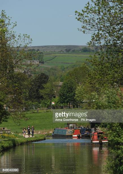 A boat makes its way along the Leeds and Liverpool Canal at Five Rise Locks Bingley West Yorkshire as the warm weather continues across the UK