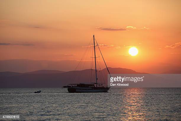 A boat makes its way out to sea on May 31 2015 in Kos Greece Migrants are continuing to arrive on the Greek Island of Kos from Turkey who's shoreline...