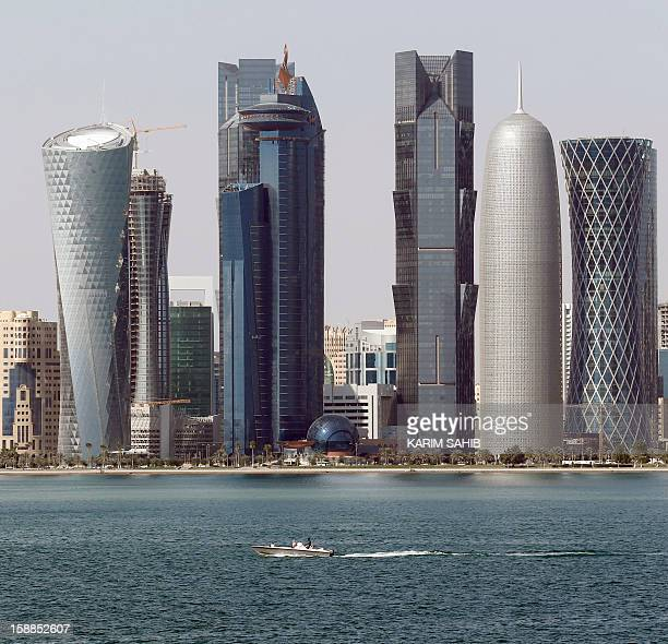 A boat makes its way with the Qatari capital Doha skyline in the background on January 1 2013 AFP PHOTO/KARIM SAHIB