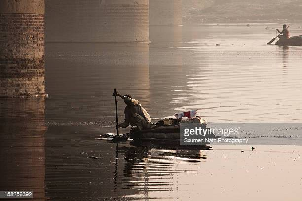 Boat man collecting filth to earn a living