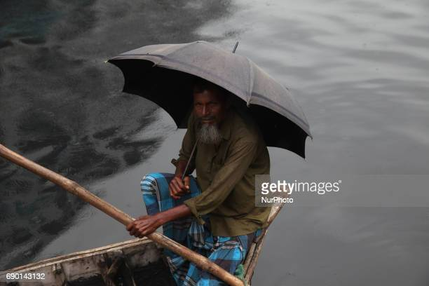 A boat man waiting or the passenger during the rainy weather at the Sdarghat launch terminal in Dhaka Bangladesh on 30 May 2017 All river transports...
