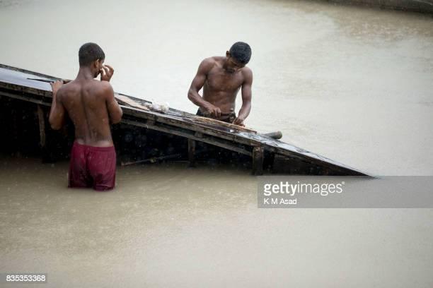 SARIAKANDHI BOGRA BANGLADESH Boat men repair their boat at Shariakandi Bogra According to authorities floods caused by heavy rainfall lashing...
